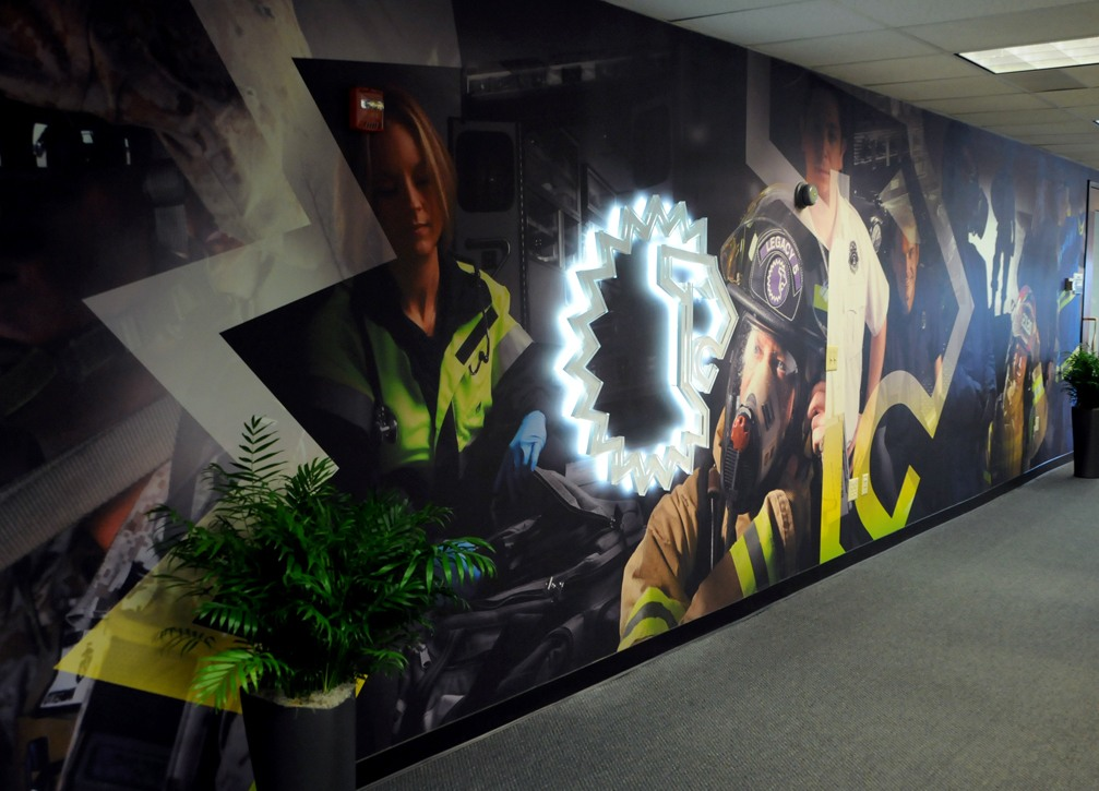 A photo of the LION log glowing on the background wall graphic on the entrance wall of the office
