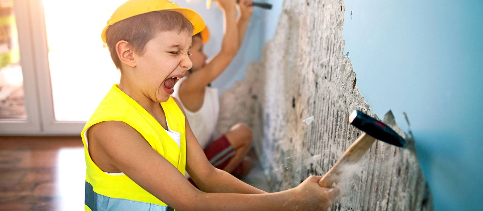 A boy dressed as a construction worker and busting through an old wall.