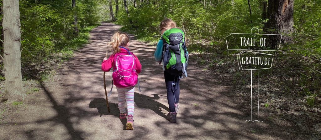 Two little girls with their backpacks and hiking sticks walking on a trail.