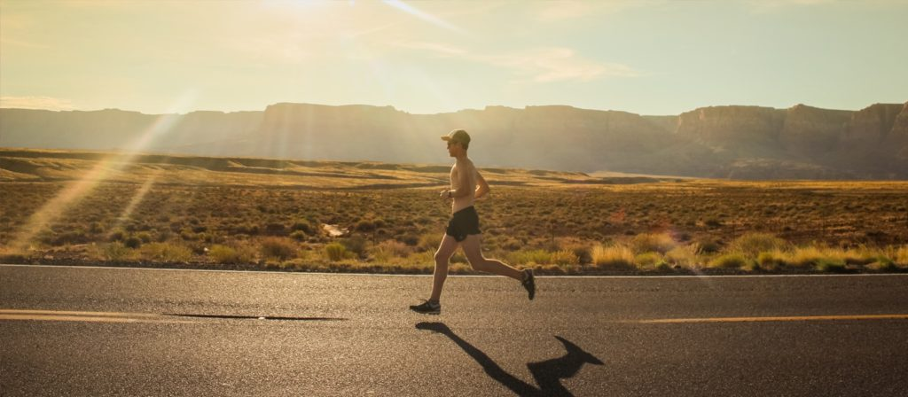 A man with a hat and no shirt jogging along the a state road surrounded by desert and some hills in the distance.